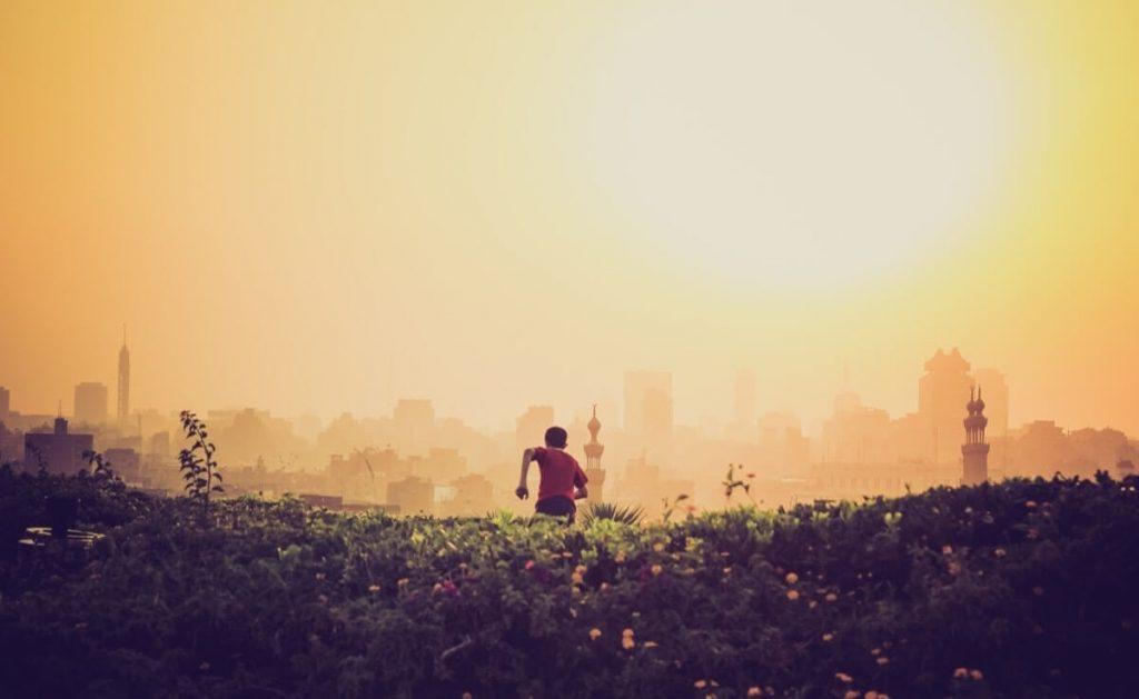 jongen en ondergaande zon met caïro op de achtergrond